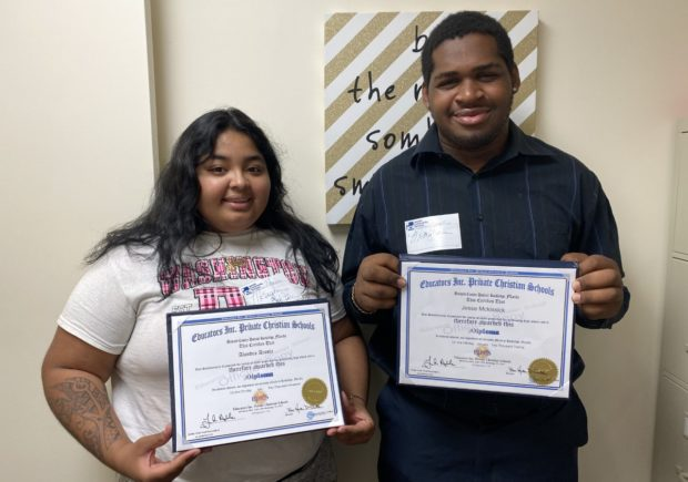 A young boy and girl holding up certificates