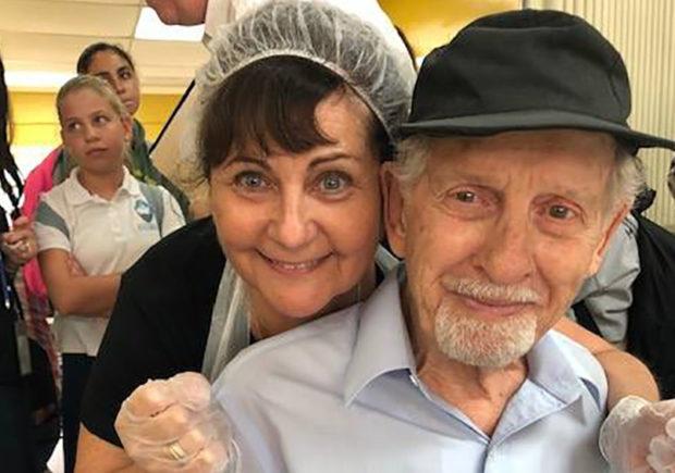 Volunteer hugging an older gentleman