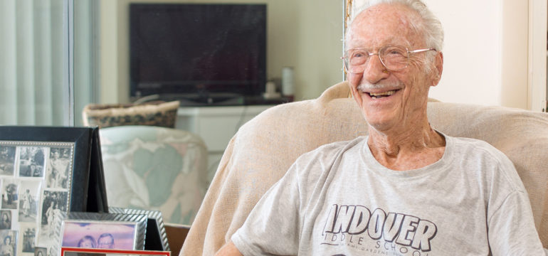 Smiling senior male sitting at home