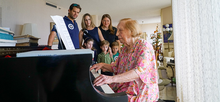 Volunteers watching an older woman playing the piano