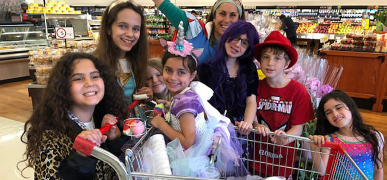 Mom and kids shopping and smiling around a shopping cart