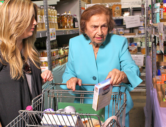 Older woman putting food into a shopping cart at the Kosher Food Bank in Miami with a woman helping her