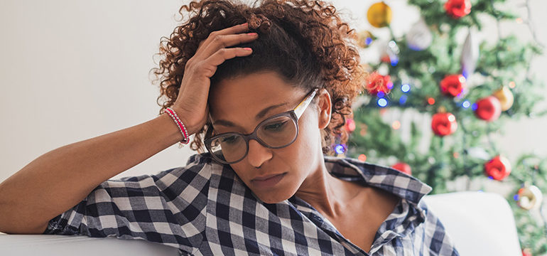 Female sitting on a couch feeling alone and abandoned during Christmas holiday