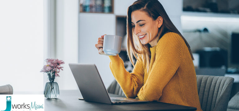 Woman sitting at home on her laptop as she holds a cup with her right hand