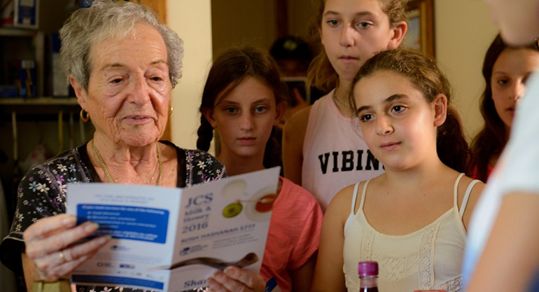 Older woman reading a brochure as young girls read behind her