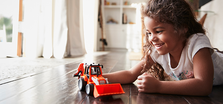 Young girl playing in her living room with a red truck
