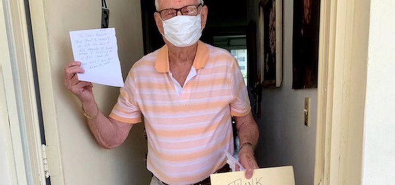Older male wearing a face mask holding a thank you JCS sign as he stands in front of his doorway