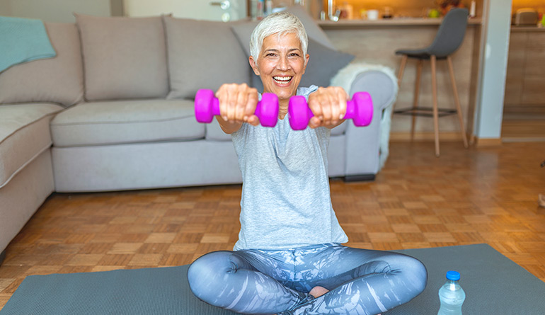 Woman working out at home, holding pink weights and smiling at the camera