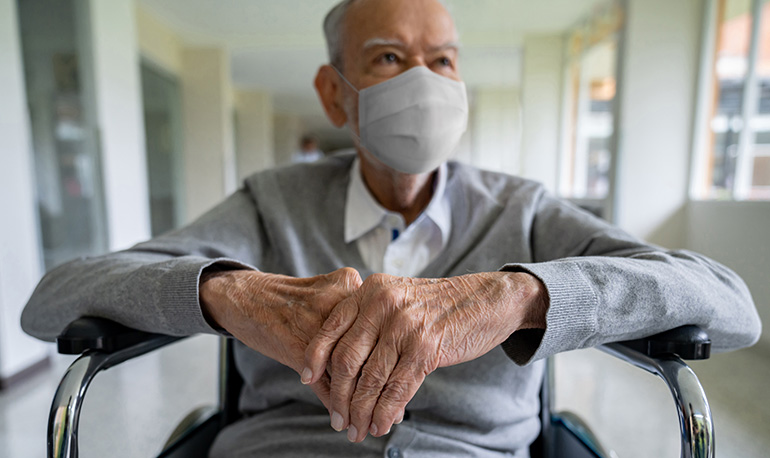 Senior adult sitting on a wheelchair wearing a face mask